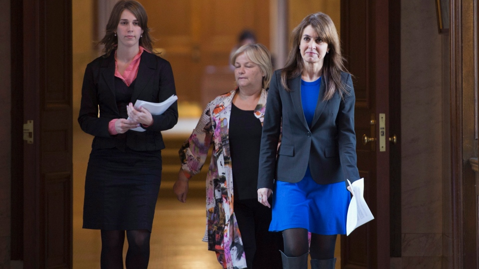Parti Quebecois MLA Veronique Hivon walks to a news conference to announce her decision to resign as Public Health and Youth Protection minister because of her pregnancy Thursday, October 18, 2012 at the legislature in Quebec City. Hivon is followed by press attache Marie Joelle Cardonneau, left, and chief of cabinet Monique Richard, centre. THE CANADIAN PRESS/Jacques Boissinot