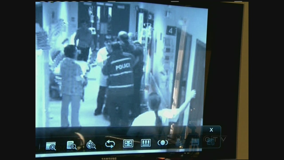 Two police officers were caught on surveillance camera trying to arrest an ER doctor for obstruction of justice in February 2012