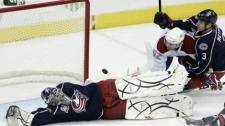 Columbus Blue Jackets goalie Mathieu Garon, left, stops a shot in front of Montreal Canadiens' Mathieu Darche (52) and Blue Jackets' Marc Methot (3) in the third period of an NHL hockey game in Columbus, Ohio, Tuesday, Nov. 2, 2010. The Blue Jackets won 3-0. (AP Photo/Paul Vernon)