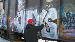 Dylan Ford spraypaints his tag 'Jays' on the side of a railcar.