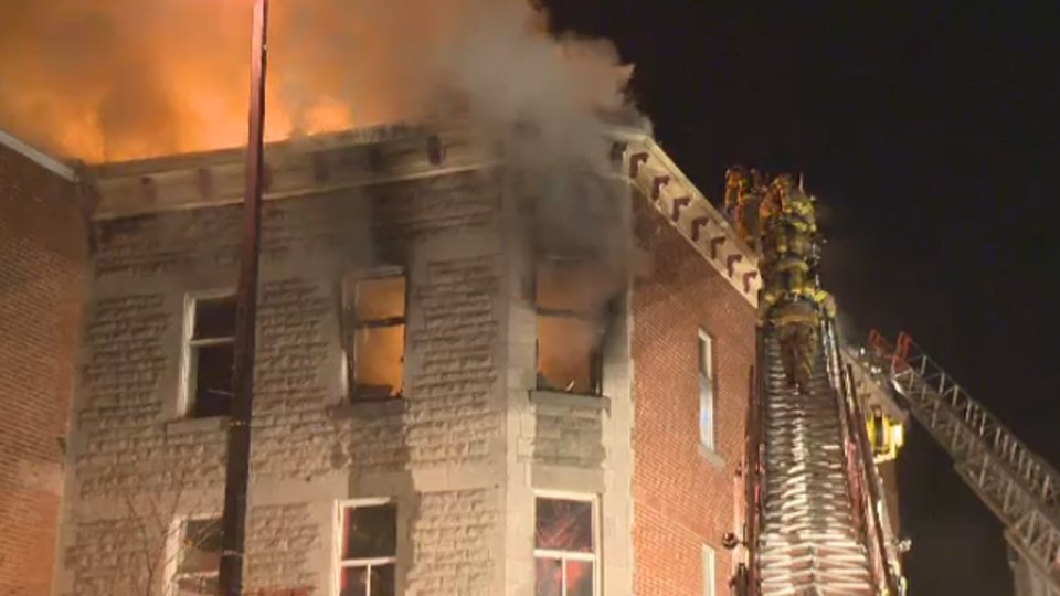 Firefighters climb onto the roof of a burning building at 3561 Ontario St. E. in Montreal (Nov. 15, 2012)