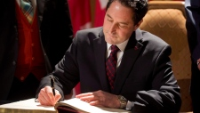 Michael Applebaum signs his name during a ceremony