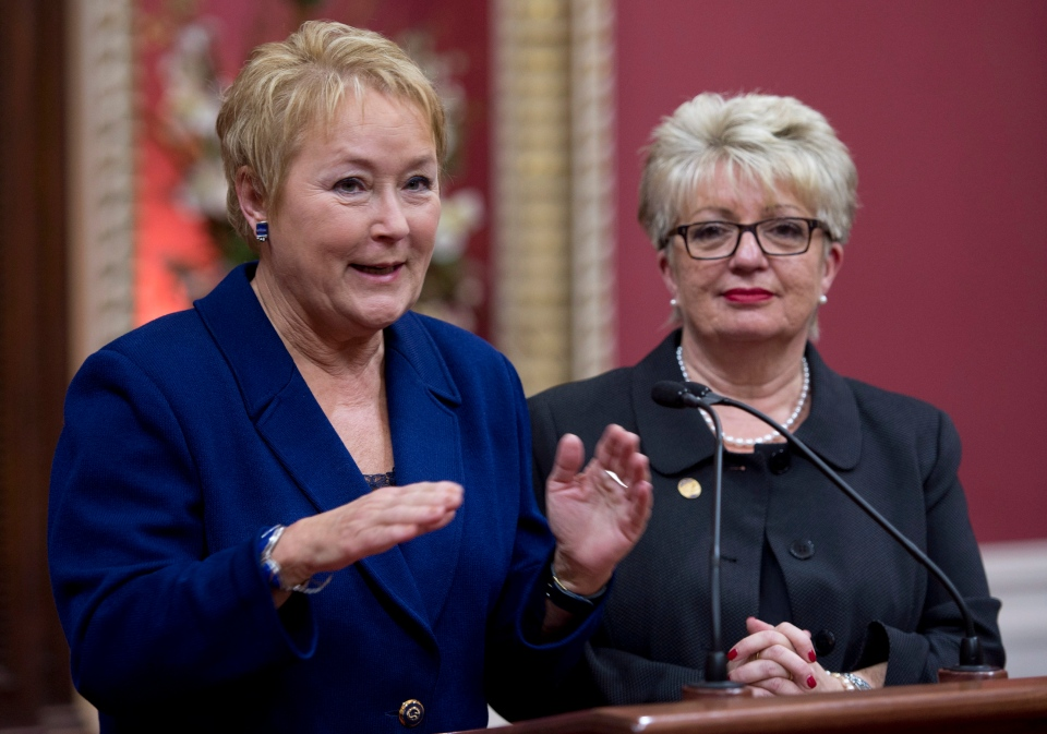 Quebec Premier Pauline Marois, flanked by Language Minister Diane De Courcy, responds to reporters' questions at the legislature in Quebec City on Dec. 5, 2012. (Jacques Boissinot / THE CANADIAN PRESS)