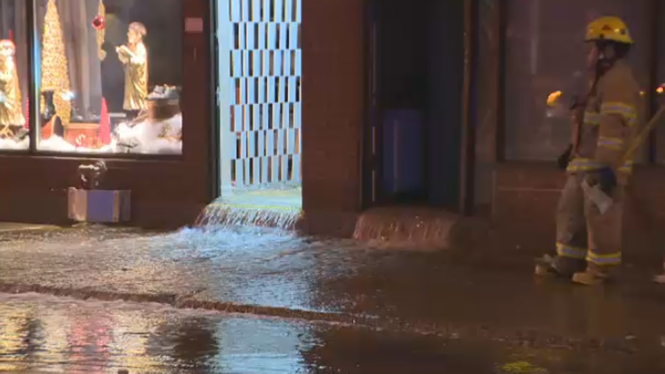A firefighter keeps watch as water spills out of a shoe store. A pipe inside the building at 2501 Belanger St. in Montreal leaked, possibly because of a malfunctioning sprinkler system. (Dec. 11, 2012)