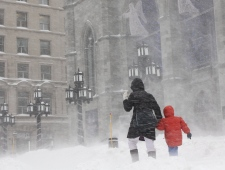 A woman walks with her child in past Notre-Dame Ba