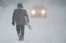 A man walks along a road near Montreal Thursday, D