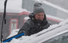 Peter Johnson clears snow from his car near Montre