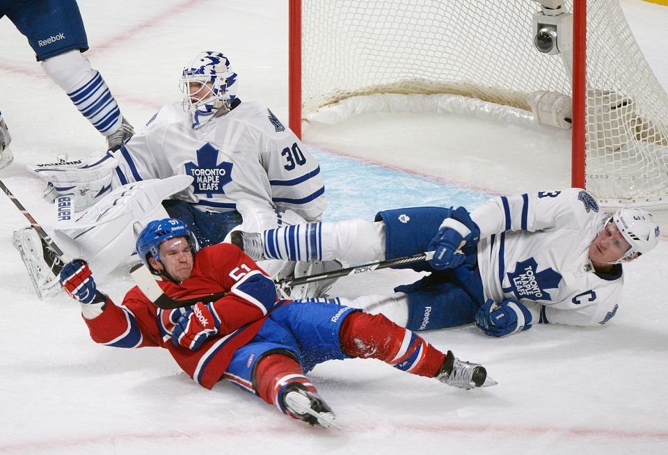 Montreal Canadiens' David Desharnais (51) slides in on Toronto Maple Leafs' goaltender Ben Scrivens and Leafs' Dion Phaneuf (3) during second period NHL hockey action in Montreal, Saturday, January 19, 2013. THE CANADIAN PRESS/Graham Hughes