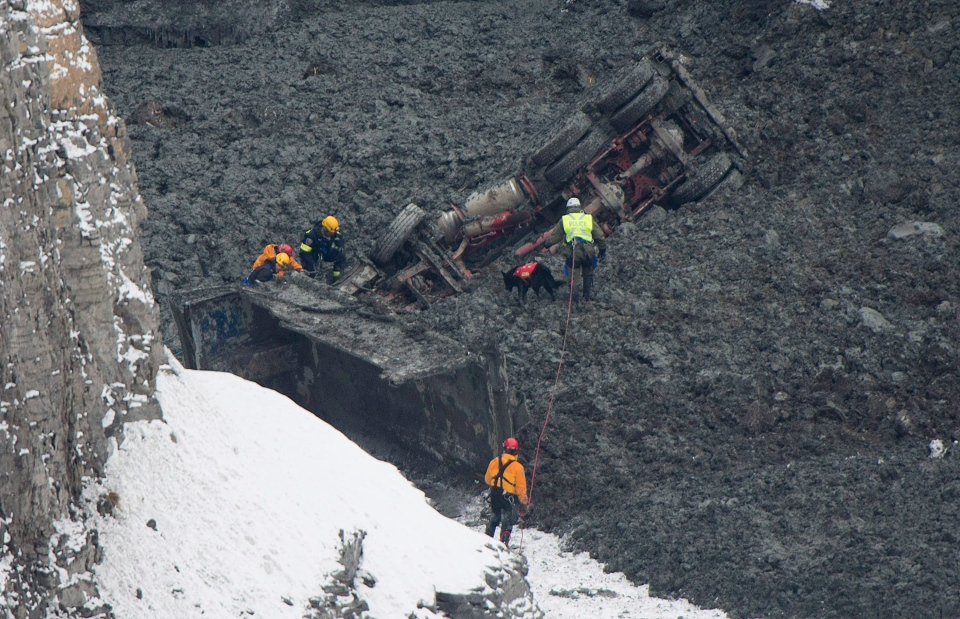 Rescuers search for missing workers in a quarry at L'Epiphanie, Que., Tuesday, January 29, 2013, following a landslide where a number of vehicles fell into the quarry. THE CANADIAN PRESS/Graham Hughes.