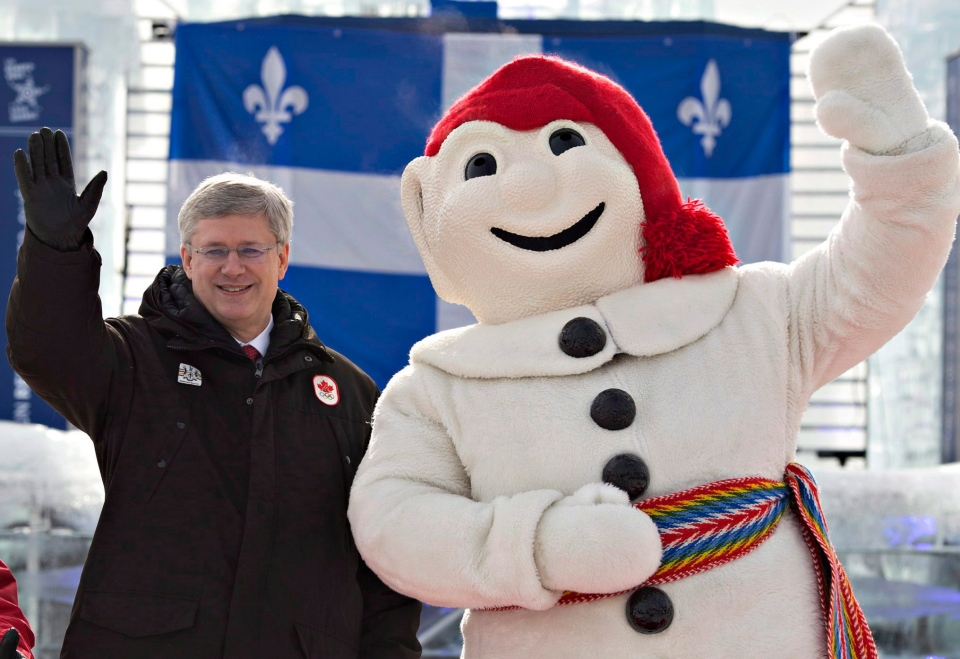 Prime Minister Stephen Harper, flanked by Quebec city Mayor Regis Labeaume, left, and Bonhomme Carnaval stand in front of the winter carnival ice castle Friday, February 1, 2013 in Quebec City. THE CANADIAN PRESS/Jacques Boissinot