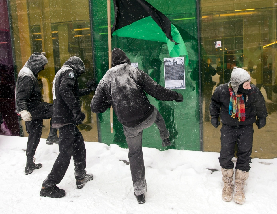 Demonstrators try to break a window at the convention centre during a protest against Quebec's developmental Plan North Friday, February 8, 2013 in Montreal. THE CANADIAN PRESS/Ryan Remiorz