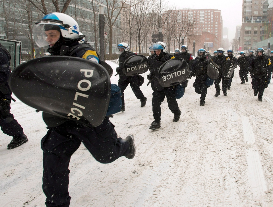Riot police chase demonstrators during a protest against Quebec's developmental Plan North on Friday, Feb. 8, 2013 in Montreal. (Ryan Remiorz/THE CANADIAN PRESS)