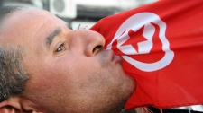 A man kisses the Tunisian flag during a demonstration in Tunis, Tunisia, against high prices and unemployment, Saturday Jan. 8, 2011. (AP Photo/Hassene Dridi)