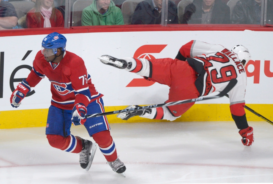 Montreal Canadiens' P.K. Subban, left, avoids a check by Carolina Hurricanes' Tim Wallace during first period NHL hockey action in Montreal Monday, February 18, 2013. THE CANADIAN PRESS/Graham Hughes