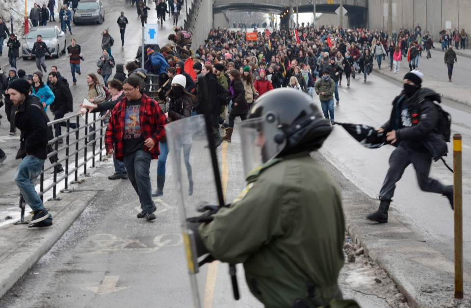 A police officer moves in on protesters during a demonstration by students in Montreal, Tuesday, Feb.26, 2013. THE CANADIAN PRESS/Ryan Remiorz