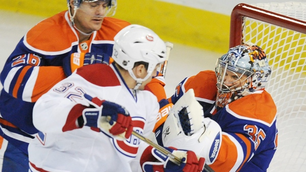 The Edmonton Oilers' Kurtis Foster, left, defends goalie Nikolai Khabibulin, right, from Montreal Canadiens', Travis Moen, during first period NHL hockey action in Edmonton, on Thursday, February 17, 2011. THE CANADIAN PRESS/John Ulan