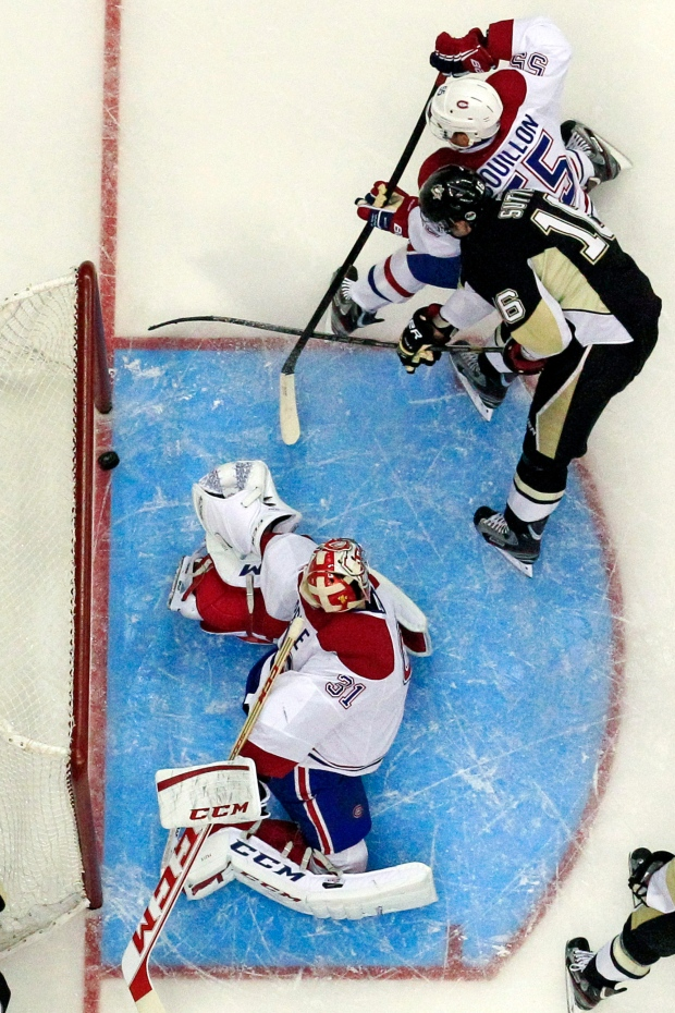 Pittsburgh Penguins center Brandon Sutter beats Montreal Canadiens goalie Carey Price with Canadiens defenseman Francis Bouillon defending during the second period of an NHL hockey game in Pittsburgh Wednesday, April 17, 2013.  (AP Photo/Gene Puskar)