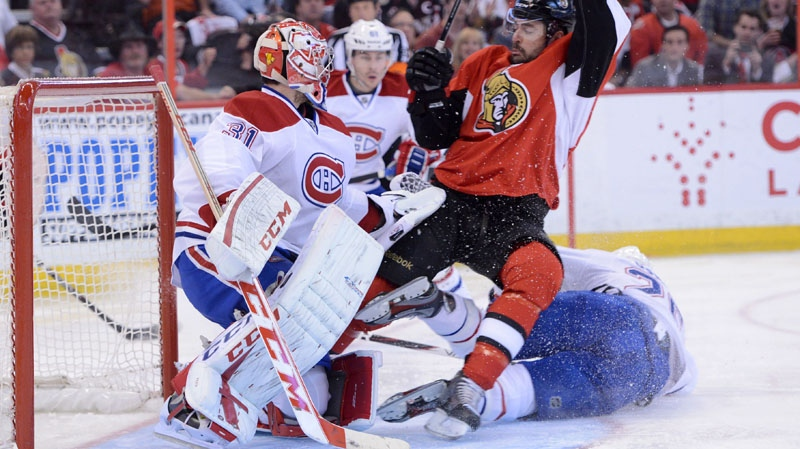 Montreal Canadiens' Josh Gorges, right, falls to the ice as he battles Ottawa Senators' Chris Phillips, centre, in front of Canadiens goalie Carey Price during first period game four NHL Stanley Cup playoffs action in Ottawa on Tuesday, May 7, 2013. THE CANADIAN PRESS/Sean Kilpatrick