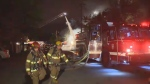 Firefighters walk past a ladder truck and hose spraying water onto a home under construction that caught fire Monday May 20, 2013.