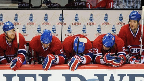 Montreal Canadiens Jeff Halpern, left to right, Mathieu Darche, Benoit Pouliot, Ryan White and Hal Gill look on from their bench during third period of an NHL hockey game against the Washington Capitals in Montreal, Saturday, March 26, 2011.The CANADIAN PRESS/Graham Hughes