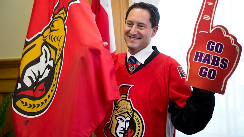 Montreal Mayor Michael Applebaum sports an Ottawa Senators jersey while showing his support for the Montreal Canadiens in his office after losing a bet to Ottawa Mayor Jim Watson Monday, May 27, 2013 in Montreal. The Montreal Canadiens lost to the Ottawa Senators in the first round of the NHL playoffs. THE CANADIAN PRESS/Paul Chiasson
