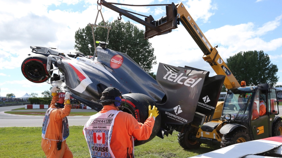 Track workers remove the car of Sauber driver Esteban Gutierrez of Mexico after a crash at the Canadian Grand Prix in Montreal, June 9, 2013. (Tom Boland / THE CANADIAN PRESS)