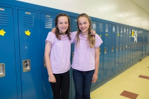Emma Merk, left, and her twin sister, Katie, one of the twenty-four sets of twins from Highcrest Middle School in Wilmette, Ill., pose for a portrait art the school, Thursday, June 6, 2013. (AP / Scott Eisen)