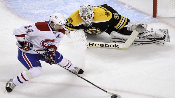 Boston Bruins goalie Tim Thomas, top, drops to the ice to make a save on a shot by Montreal Canadiens center Tomas Plekanec during the second period of a first-round NHL hockey playoff game in Boston, Thursday, April 14, 2011. (AP Photo/Charles Krupa)