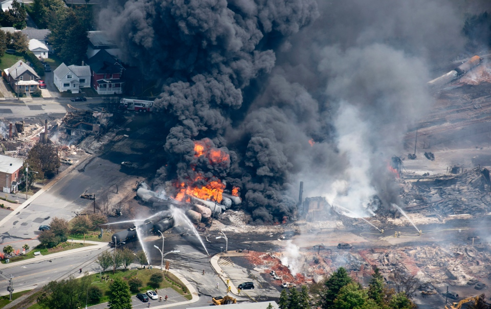 Smoke rises from railway cars that were carrying crude oil after derailing in downtown Lac Megantic, Que., Saturday, July 6, 2013. THE CANADIAN PRESS/Paul Chiasson