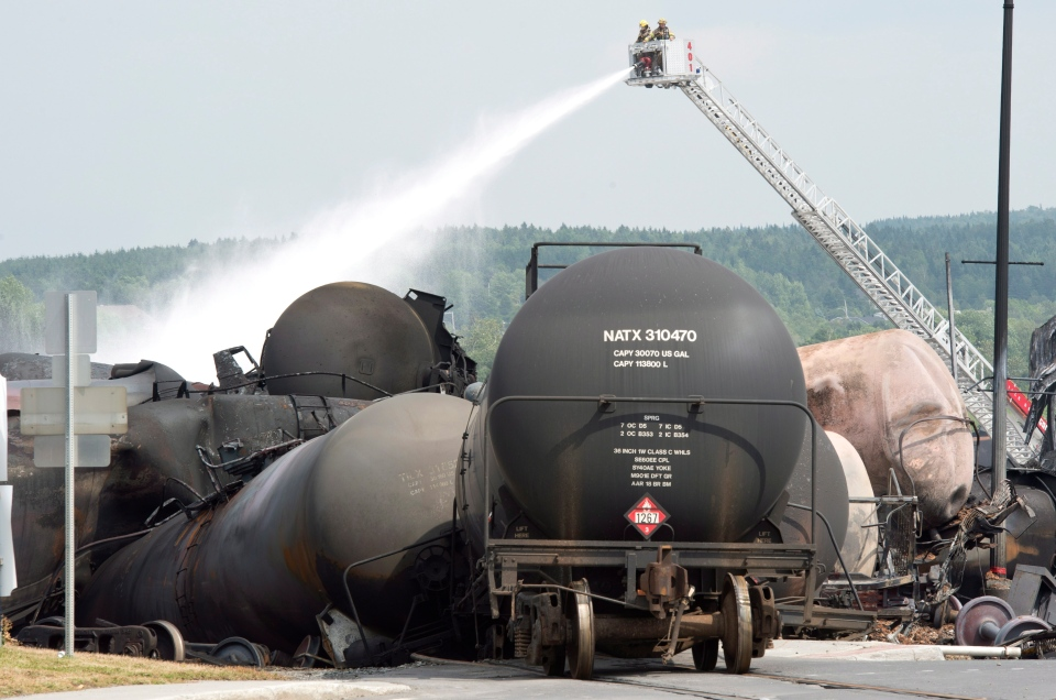 Fire fighters keep watering railway cars the day after a train derailed causing explosions of railway cars carrying crude oil Sunday, July 7, 2013, in Lac Megantic, Que. (Paul Chiasson /The Canadian Press)
