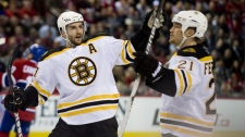 Boston Bruins' Andrew Ference (21) celebrates with teammate Patrice Bergeron, after scoring against the Montreal Canadiens during second period Game 4 NHL Stanley Cup playoff hockey action in Montreal, Thursday, April 21, 2011. (THE CANADIAN PRESS/Graham Hughes)