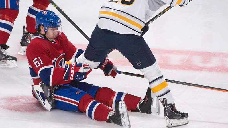 Montreal Canadiens defenseman Raphael Diaz (61) holds onto Buffalo Sabres' Zemgus Girgensons (28) during first period NHL hockey action in Montreal, Saturday, December 7, 2013 THE CANADIAN PRESS/Peter McCabe