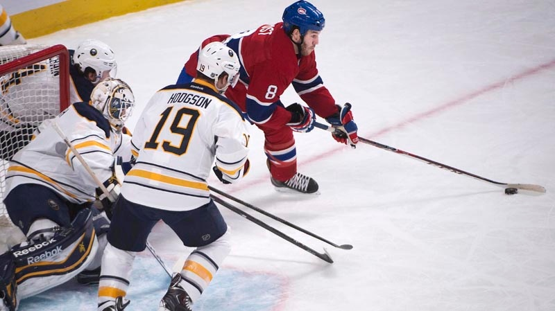 Montreal Canadiens' Brandon Prust (8) looks to shoot as Buffalo Sabres' Cody Hodgson (centre) and goalie Jhonas Enroth look on during first period NHL hockey action in Montreal, Saturday, December 7, 2013. THE CANADIAN PRESS/Peter McCabe