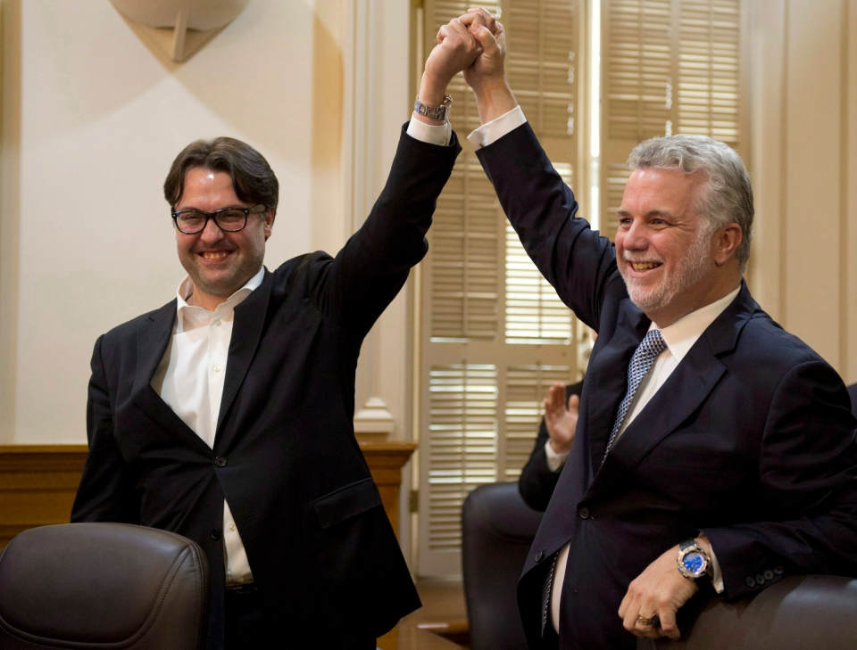Quebec Liberal Leader Philippe Couillard, right, raises the hand of Viau riding candidate David Heurtel as they enter a party caucus meeting, Wednesday, November 13, 2013 at the legislature in Quebec City.  THE CANADIAN PRESS/Jacques Boissinot