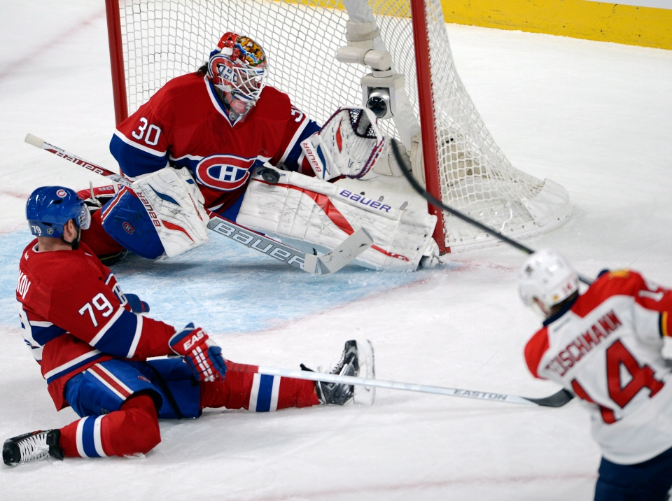 Montreal Canadiens goalie Peter Budaj (30) stops Florida Panthers left wing Tomas Fleischmann (14) as Montreal Canadiens defenceman Andrei Markov (79) moves in during first period National Hockey League action Sunday, December 15, 2013 in Montreal.THE CANADIAN PRESS/Ryan Remiorz