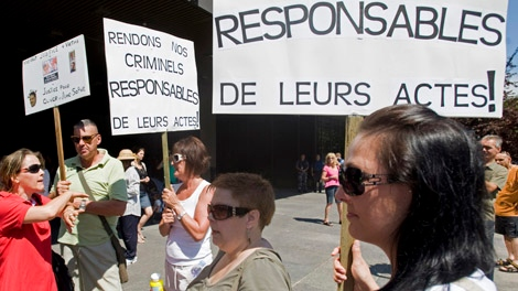 People hold up signs at a demonstration in Montreal Saturday, August 6, 2011 protesting the verdict handed down to Turcotte who was found not criminally responsible in the stabbing deaths of his two children. THE CANADIAN PRESS/Graham Hughes
