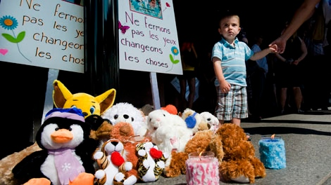 Jake Ryan, 2, stands next to a makeshift shrine in memory of Anne-Sophie and Olivier Turcotte during a demonstration in Montreal Saturday, August 6, 2011 protesting the verdict handed down to Guy Turcotte who was found not criminally responsible in the stabbing deaths of his two children. THE CANADIAN PRESS/Graham Hughes