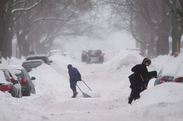 People clear snow from around their cars on a street in Montreal Sunday, December 22, 2013. (Graham Hughes / THE CANADIAN PRESS)