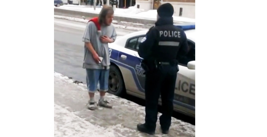 This image, taken from a YouTube video shot in Montreal on Thursday, shows a police officer speaking harshly to a homeless person.