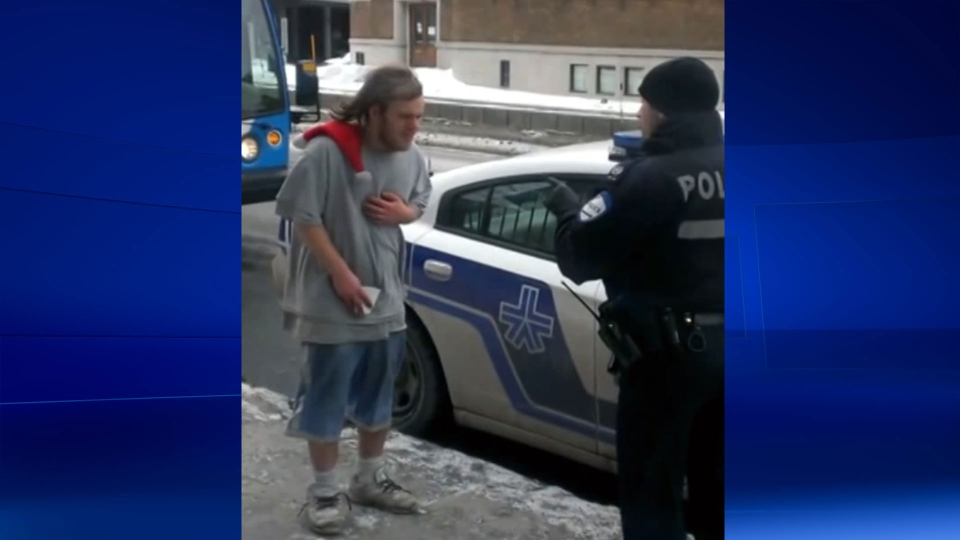 An unidentified Montreal police officer is seen speaking to a homeless man in this image taken from a YouTube video uploaded by Omar Tunisiano.