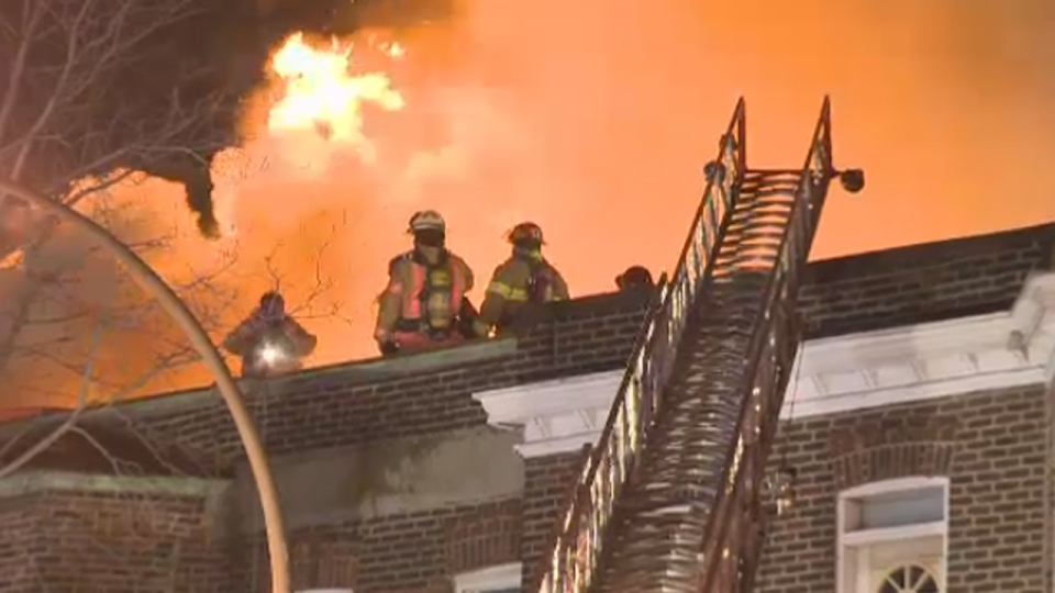 Flames burst through the roof of a St. Jacques St. building as firefighters look on (Jan 10, 2014)