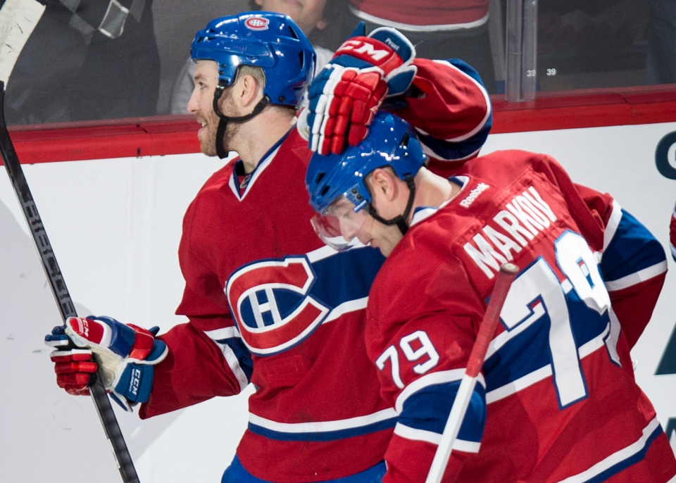 Montreal Canadiens' Andrei Markov is congratulated by teammate Brandon Prust following a goal against the Chicago Blackhawks during second period NHL hockey action Saturday, January 11, 2014 in Montreal. Markov went on to score the winning goal in overtime to beat the Blackhawks 2-1. THE CANADIAN PRESS/Paul Chiasson