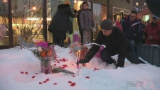 A man plants a candle in the snow at Fabre metro