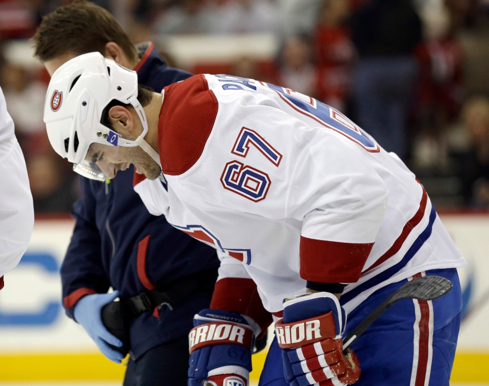 Montreal Canadiens' Max Pacioretty is assisted off the ice following an injury during the first period of an NHL hockey game against the Carolina Hurricanes in Raleigh, N.C., Saturday, Feb. 8, 2014. (AP Photo/Gerry Broome)