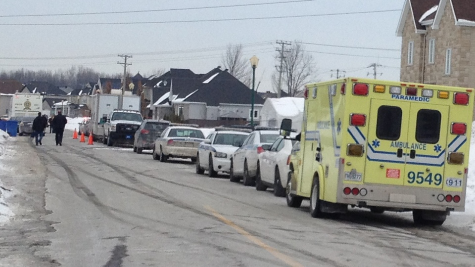 An ambulance is parked near a home in Terrebonne where two bodies were found as investigators walk down the street (CTV Montreal/George Giannelis)