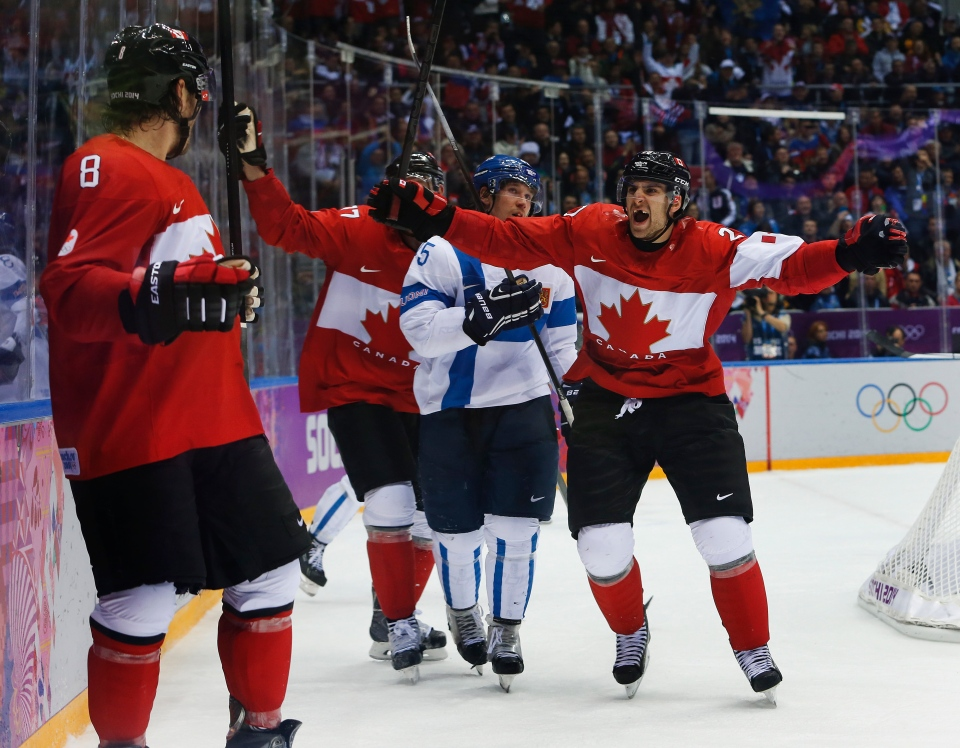 Team Canada forwards John Tavares, right, and Jeff Carter, second from left, celebrate with defenseman Drew Doughty (8) after Doughty scored a sudden death overtime goal against Finland during a men's ice hockey game at the 2014 Winter Olympics, Sunday, Feb. 16, 2014, in Sochi, Russia. Canada won 2-1. (AP Photo/Mark Humphrey)