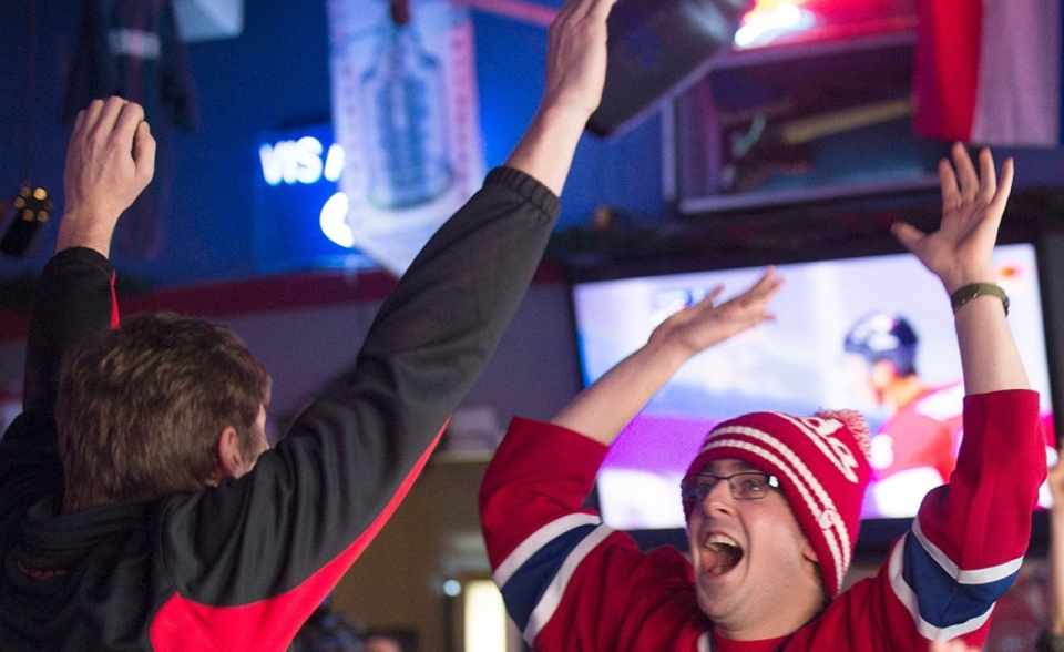 Hockey fans celebrate as team Canada scores against Swedan in the 2014 Sochi Winter Olympic gold medal game at PJ's sports bar in Montreal, Sunday, February 23, 2014. THE CANADIAN PRESS/Graham Hughes