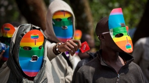 Kenyan gays and lesbians and others supporting their cause wear masks to preserve their anonymity and one holds out a condom, as they stage a rare protest, against Uganda's increasingly tough stance against homosexuality and in solidarity with their counterparts there, outside the Uganda High Commission in Nairobi, Kenya, Monday, Feb. 10, 2014. (AP / Ben Curtis)