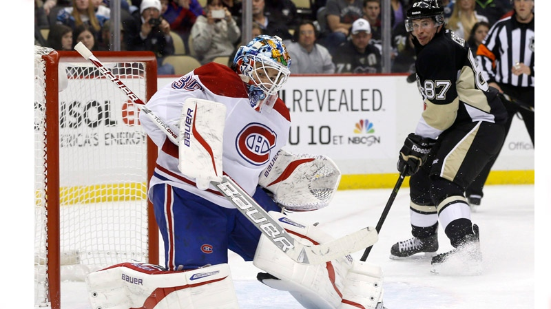 Montreal Canadiens goalie Peter Budaj, of Slovakia, stops a shot as Pittsburgh Penguins' Sidney Crosby (87) watches during the second period of an NHL hockey game, Thursday, Feb. 27, 2014 in Pittsburgh. The Canadiens won 6-5 in a shootout. (AP Photo/Keith Srakocic)