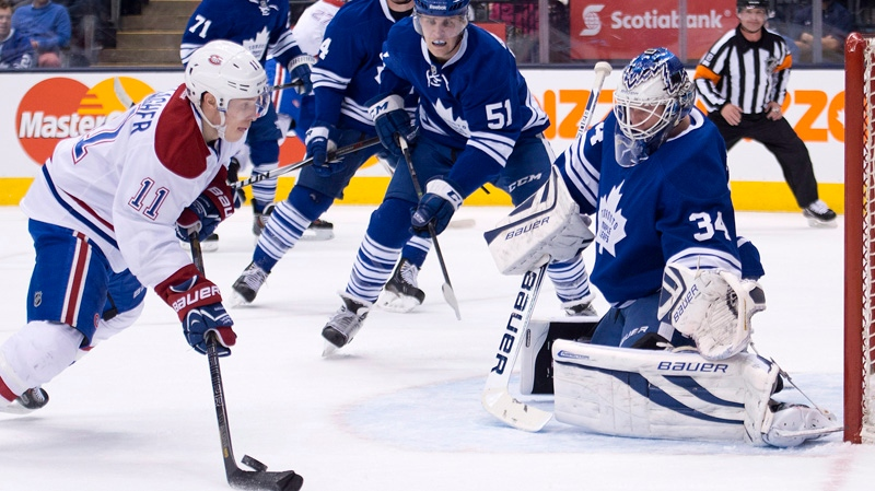 Toronto Maple goalie James Reimer, right, watches as Leafs Montreal Canadiens forward Brendan Gallagher, left, miss plays the puck during first period NHL hockey action in Toronto on Saturday, March 22, 2014. THE CANADIAN PRESS/Nathan Denette